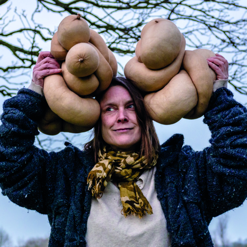 Artist Sarah Lucas in a field posing with her work.