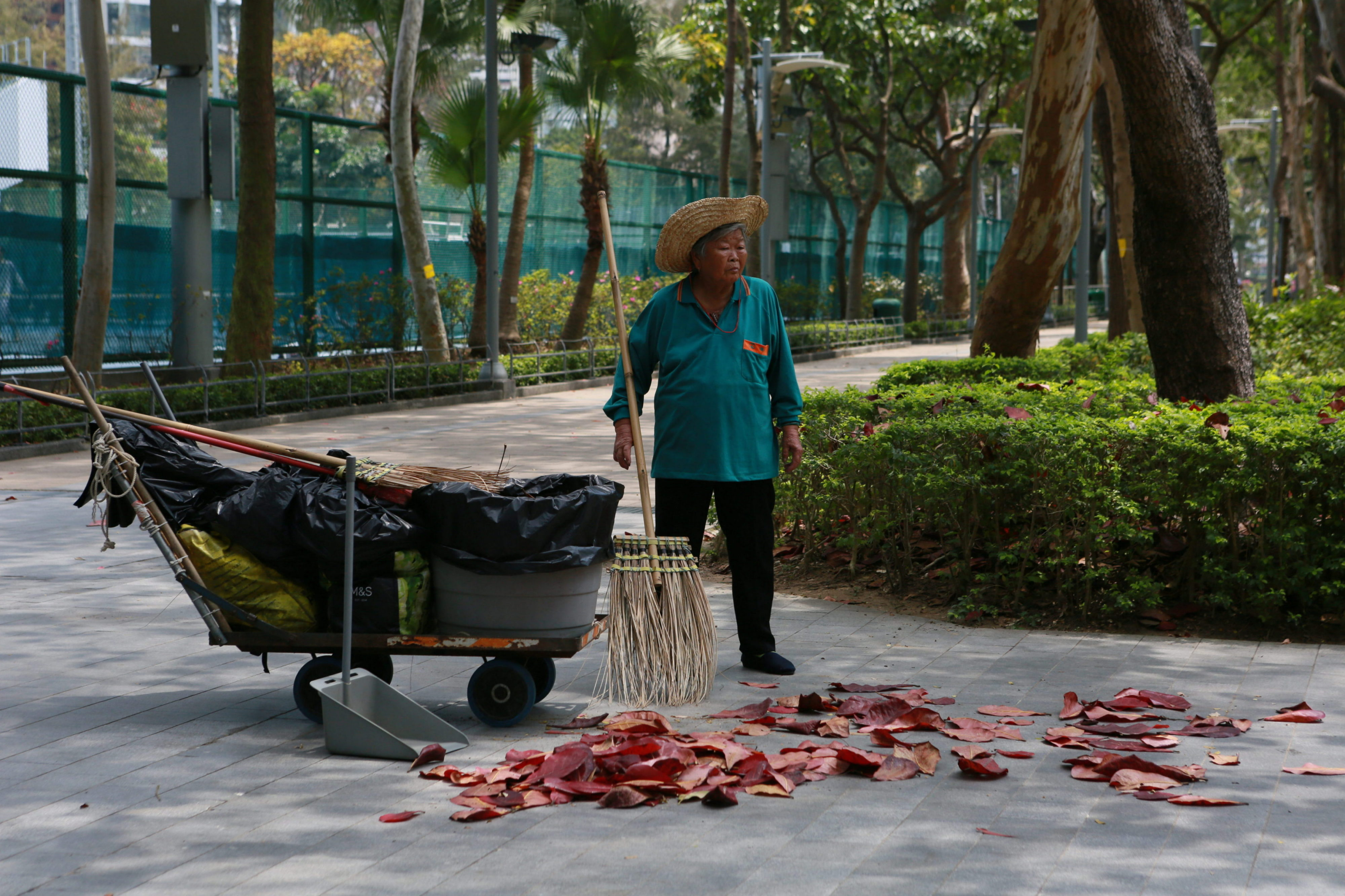 A woman clears up leaves in a park in Hong Kong. © Paul Jay, 2017.