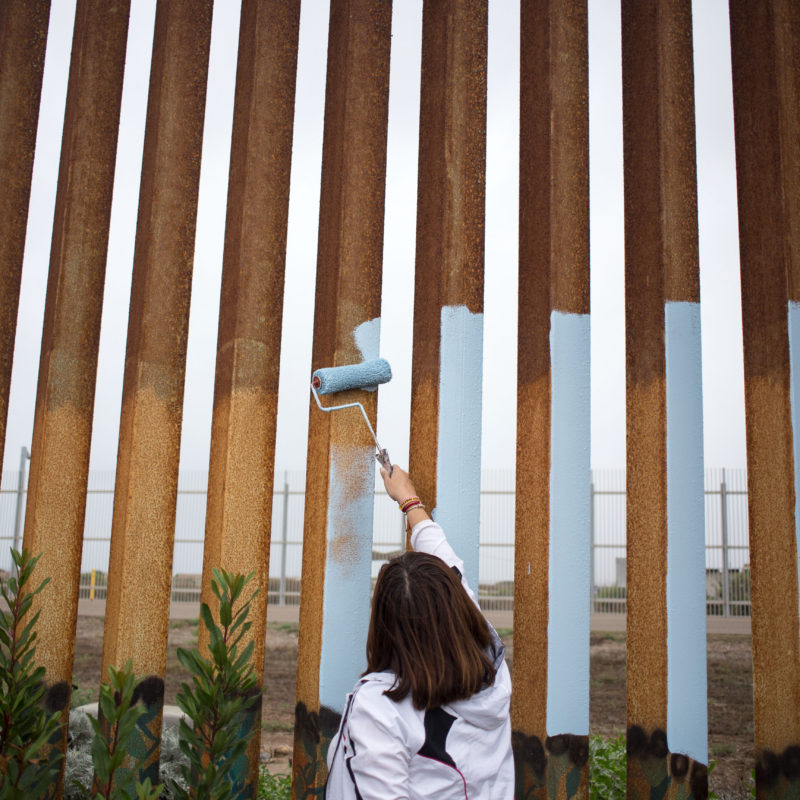 Painting the US/Mexico border fence at Playas de Tijuana. © Guillermo Arias, 2016
