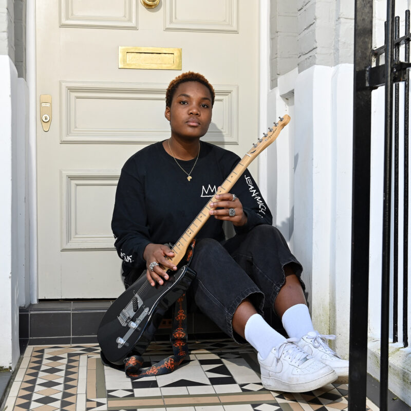 Arlo Parks during Lockdown at the front door of her apartment with cat and guitar on Tuesday 19 May 2020. Photographer: Mark Allan Loftus Media © BBC